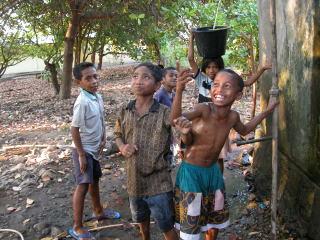 Kinderen bij een waterpomp van Plan International.